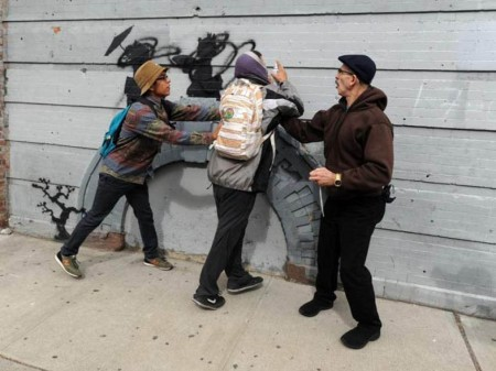 The defacer of Banksy's work is quickly apprehended by bystanders.